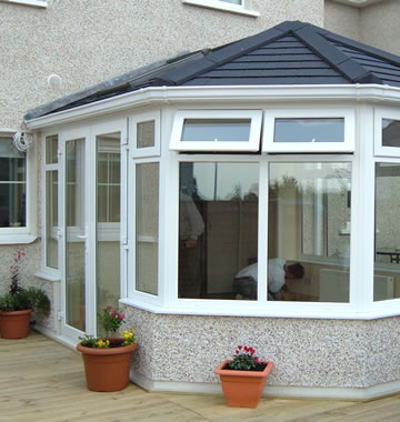 Conservatory with black tiled roof and white windows